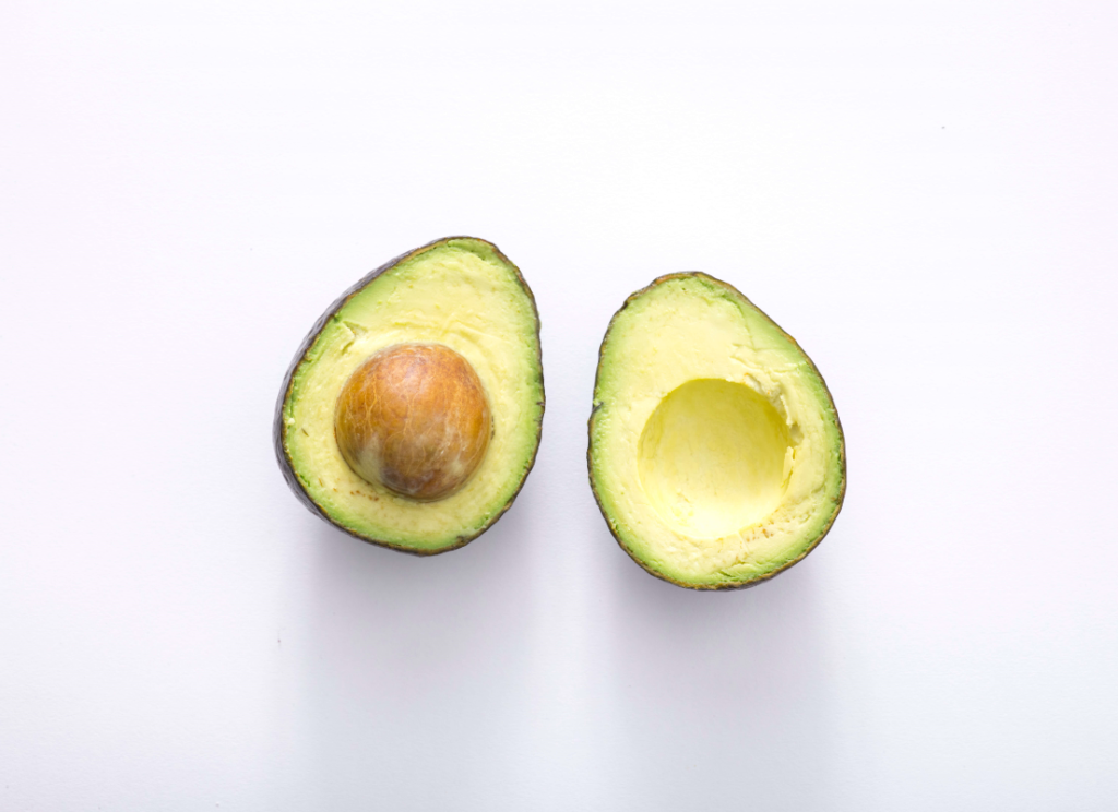 avocado cut in half on white table