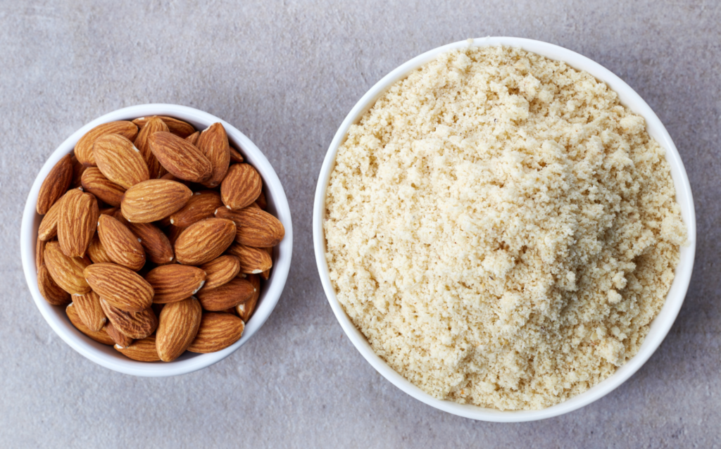 Bowl of almond flour and bowl of almonds from top view