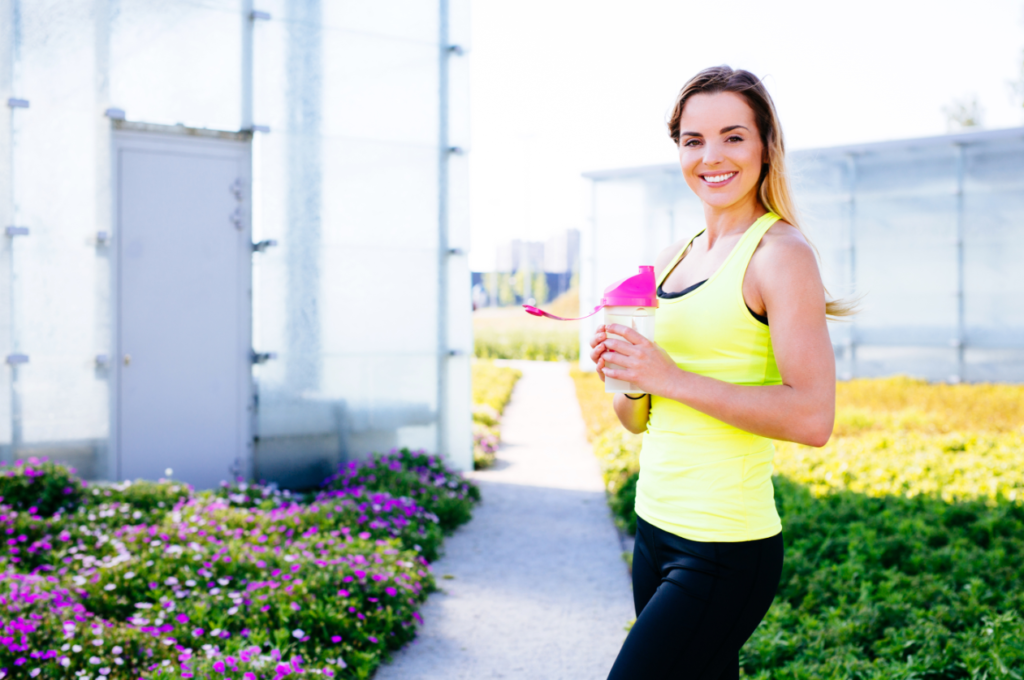 Young happy woman drinking water after runnning
