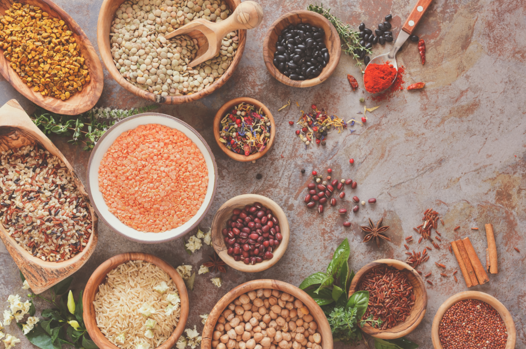 Assortment of legumes, grain and seeds. Various types of grains, rice, legumes spices and herbs in bowls on rustic table, top view