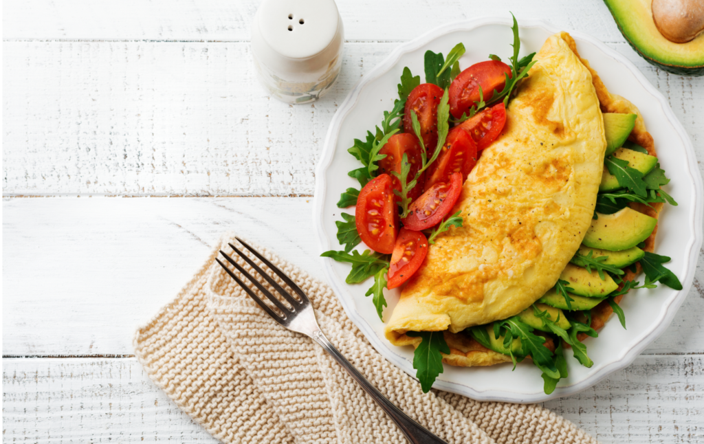 Omelette with avocado, tomatoes and arugula on white ceramic plate