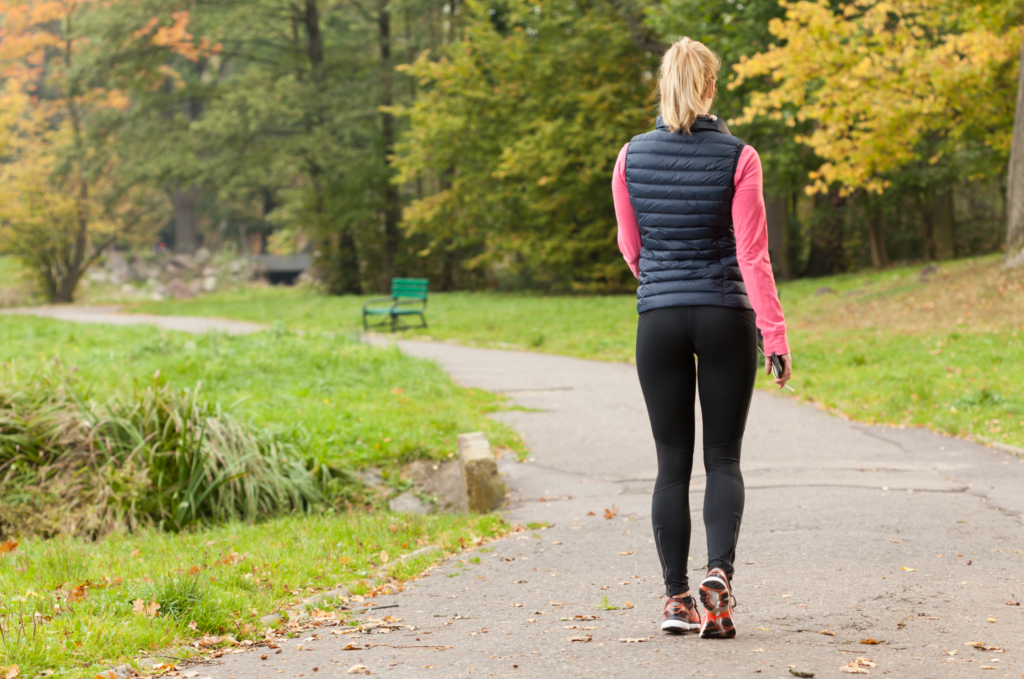 Fit woman walking in park during autumn time