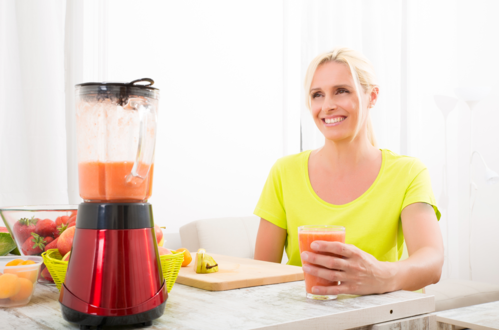 woman enjoying a smoothie or juice with fruits in the kitchen
