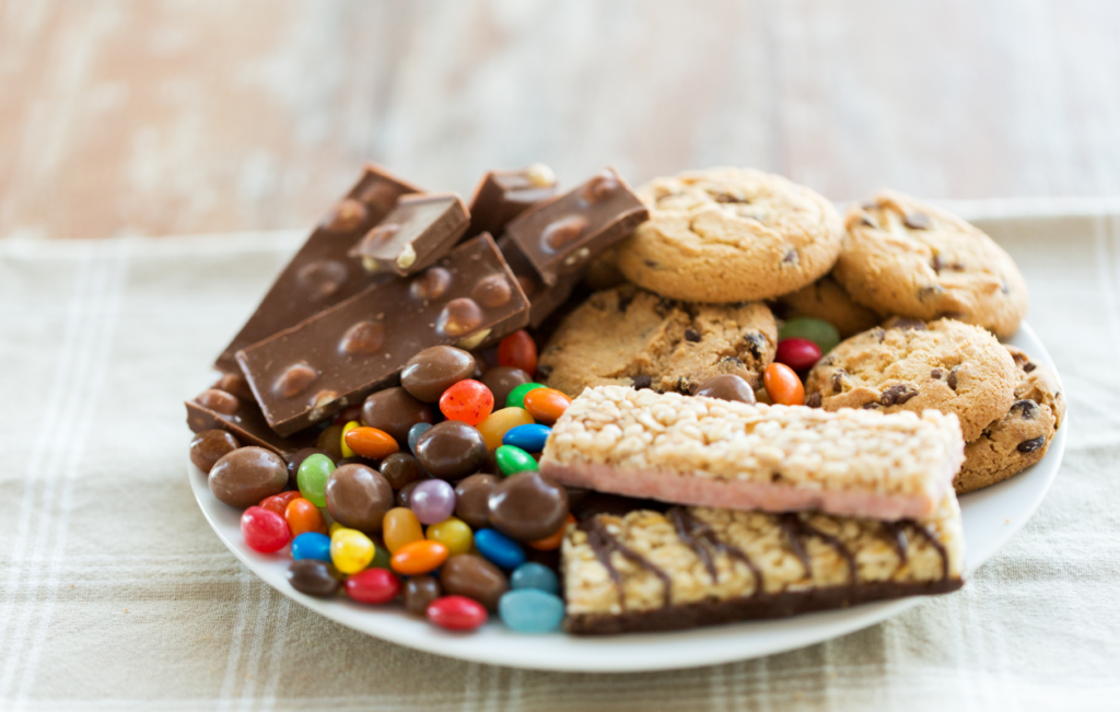 close up of chocolate, oatmeal cookies, candies and muesli bars on plate
