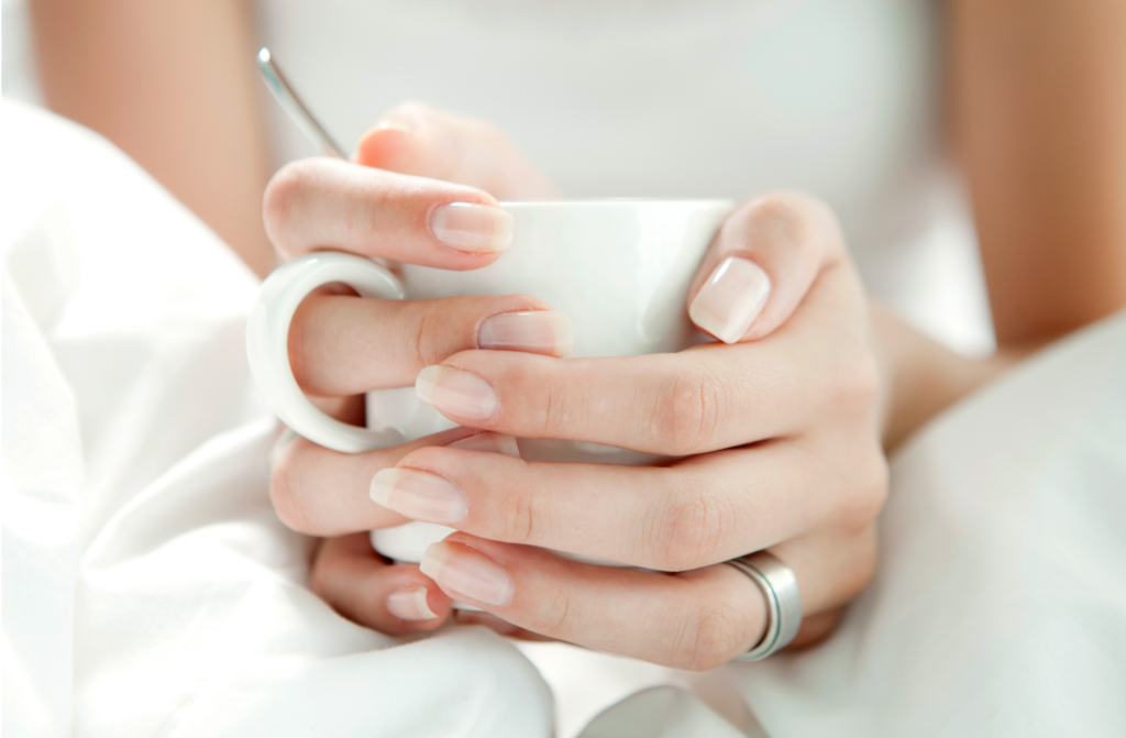 hands holding a white mug